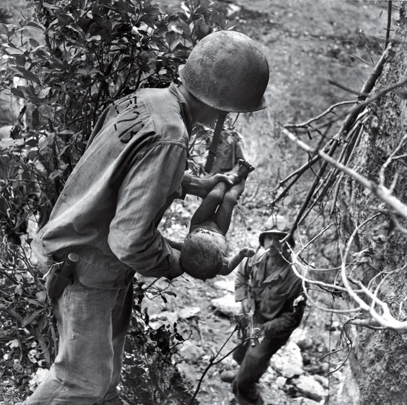 Американский морпех с ребенком в руках в джунглях на Сайпане