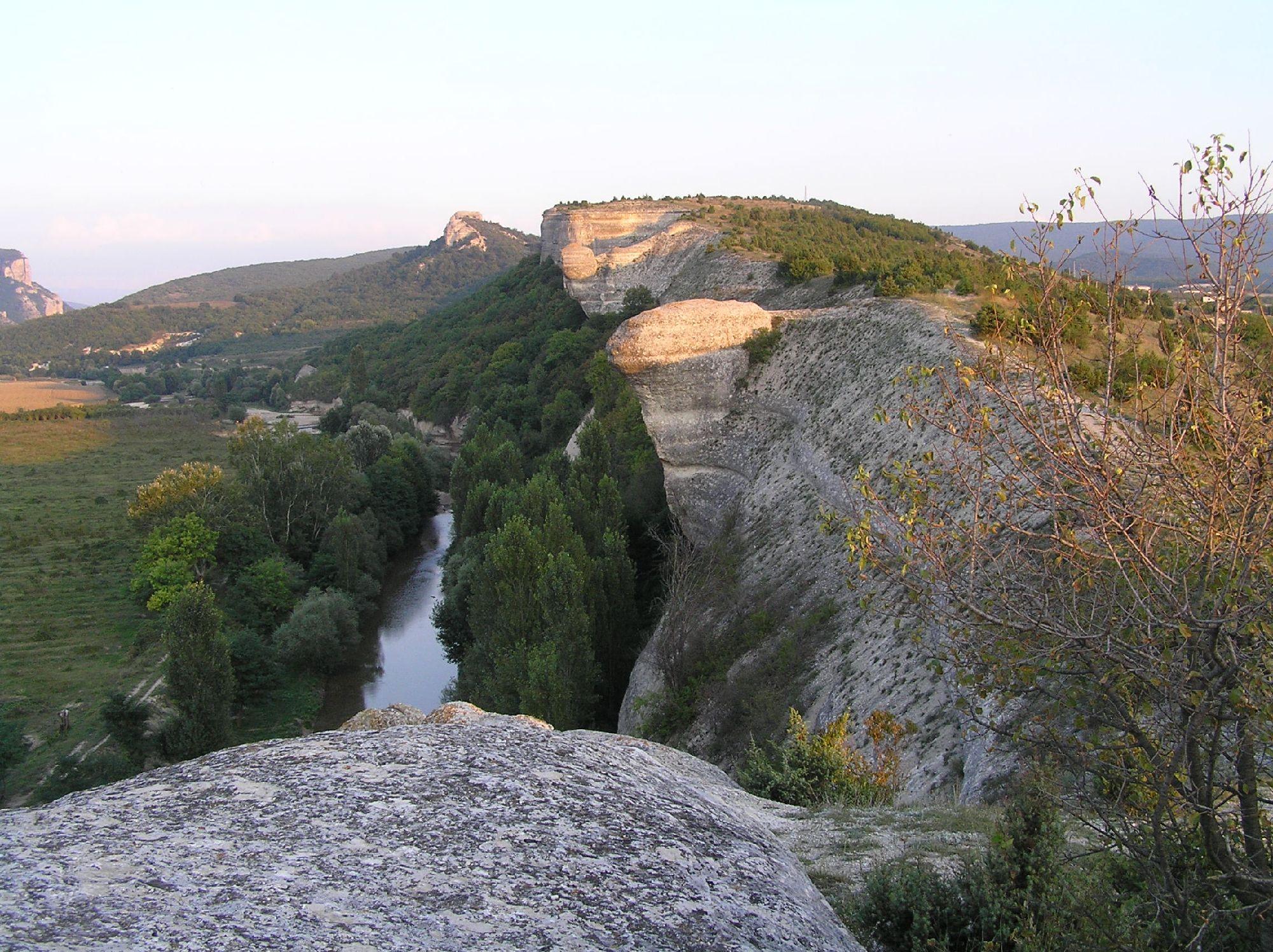 Левее (и чуть сзади, к северу) этого хребта оканчивается равнинная часть степного Крыма и начинается Крым горный. Правее Мангуп-Кале. Предзакатное фото 2005 года.