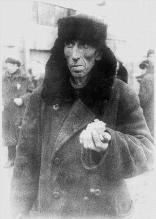 блокада Ленинграда Житель города Ленинграда возле булочной после получения хлебного пайка. 1942