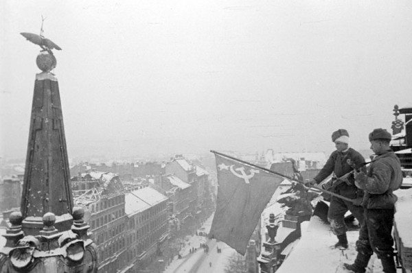 Советские бойцы вывешивают советский флаг на одном из зданий освобожденного от гитлеровцев Будапешта