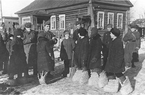 Школьники освобожденного Гжатска показывают красноармейцам немецкие «эрзац-валенки»