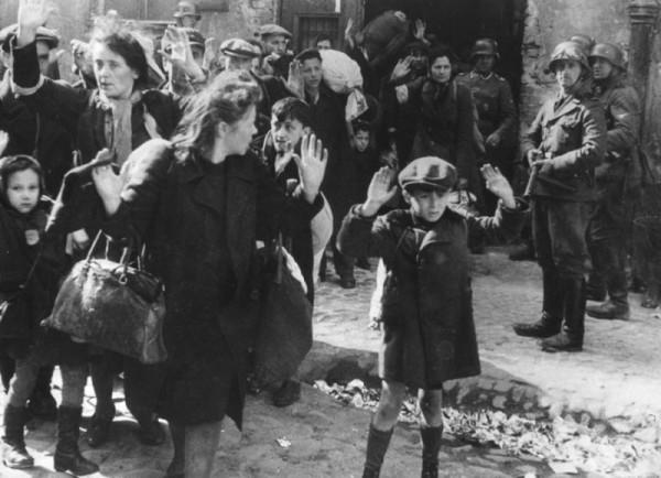 Группу евреев, в том числе маленького мальчика, выводят из Варшавского гетто в сопровождении немецких солдат. Фотография сделана 19 апреля 1943 года.