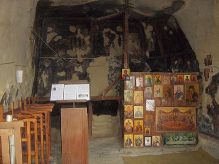 Преподобный Созомен Кипрский, место подвигов. Внутри пещерного храма. Стена, увешанная иконами - импровизированный иконостас. За ней — алтарь