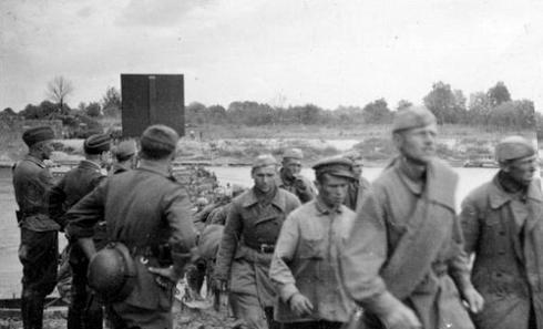 Первые советские военнопленные под наблюдением немецких солдат направляются на запад по мосту через реку Сан у города Ярослав. Время съемки 22.06.1941