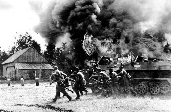 _Немецкие солдаты, поддерживаемые БТР, вступают в горящую русскую деревню во время немецкого вторжения в Советский Союз (26 июня 1941 года)
