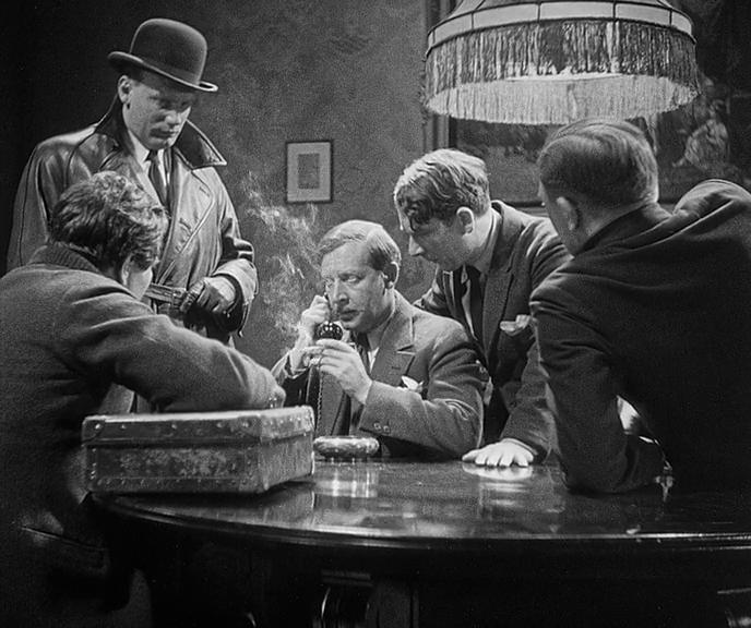 """Кадр из фильма """"М убийца"""". Стоит, в шляпе и кожаном пальто - Густаф Грюндгенс."""