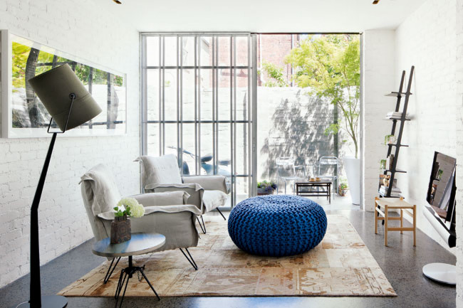 home life cococozy white brick wall living room blue knitted pouf armchairs french doors leading to patio terrace