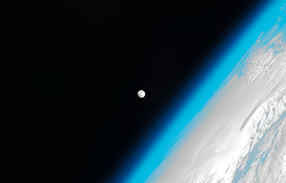 This stunning photo shows the moon and Earth's atmosphere as seen from the International Space Station.