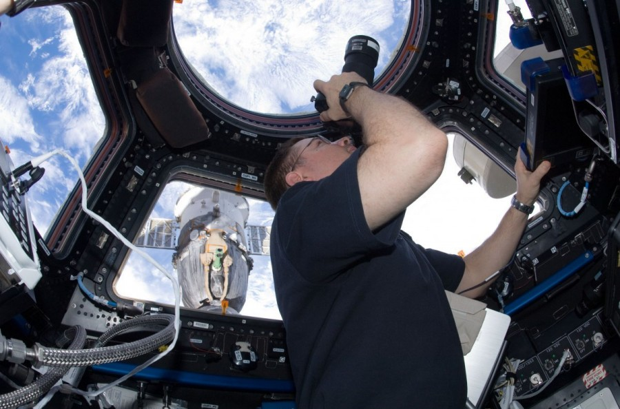 Mission Commander Douglas Wheelock aims a camera out of one of the windows in the Cupola