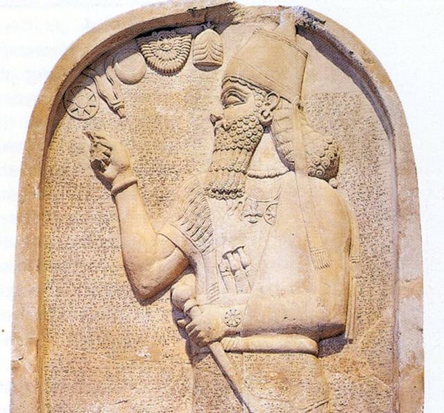 Ассирийский  царь  указывает на  символ бога Солнца