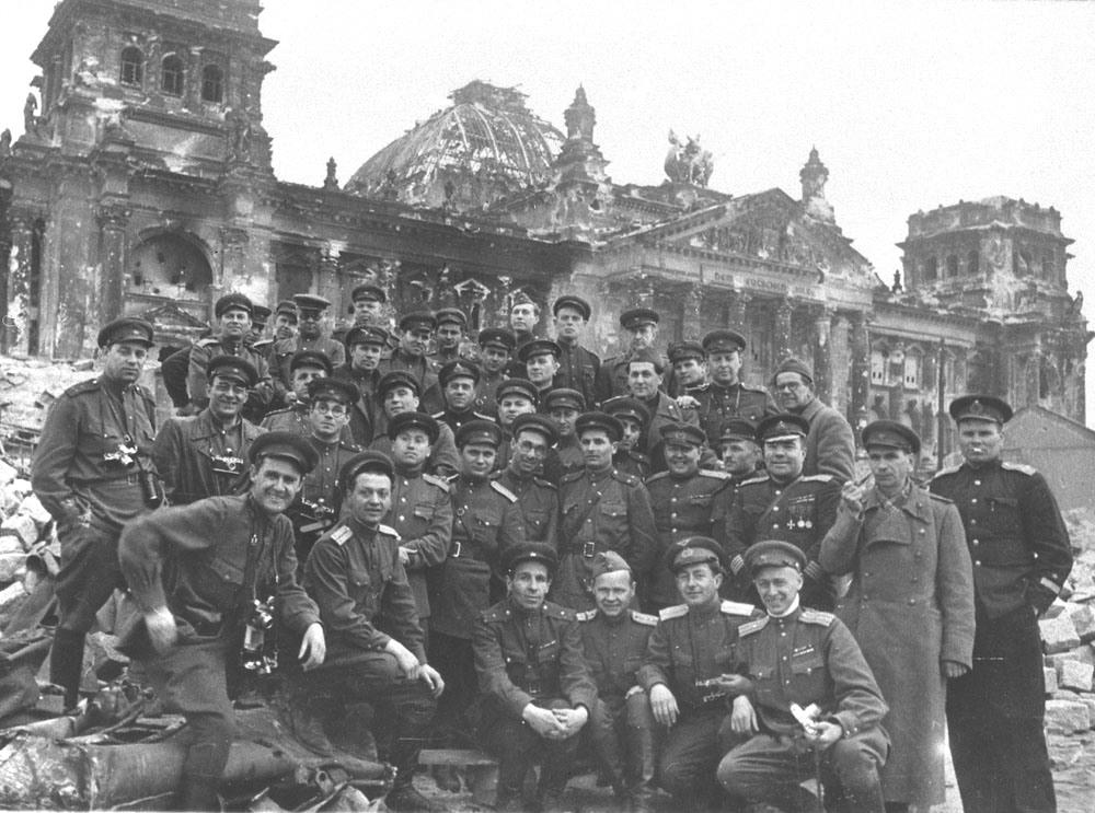 Писатель, драматург, военный корреспондент Всеволод Вишневский (третий справа, второй ряд) с товарищами на ступенях рейхстага, май 1945 года.