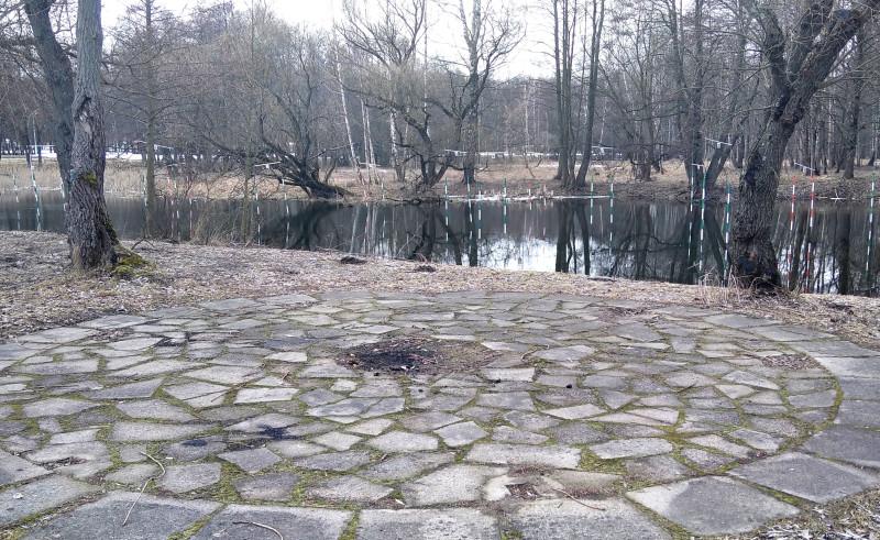 У самой реки благоустроенная площадка для костра. за кадром — скамьи и урны. Над рекой вывешены фонарики.