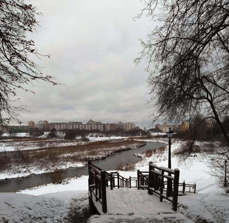 За мостиком открывается пойма реки и панорама микрорайона.