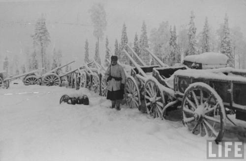 Finnish soldier guarding line of Russian carts captured in the Second Battle of Suomussalami during the Russo-Finnish War.