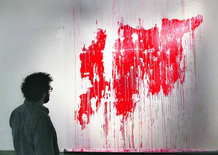 Посетитель художественной выставки, прошедшей в Объединённых Арабских Эмиратах, рассматривает полотно, на котором изображены вполне узнаваемые очертания Сирии, раздираемой сегодня кровавой войной...