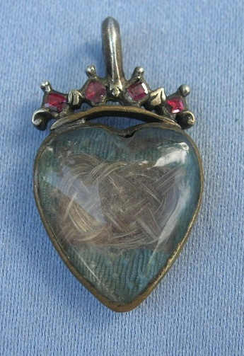 Mourning pendant, mid-18th C. Gold or brass metalwork with garnet crown and hair work encased in crystal.