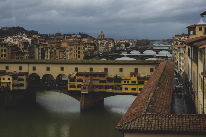 Из окна галереи Уффици видать сразу несколько мостов через реку Арно. Самый ближайший — Понте Веккьо, по верху которого проходит коридор Вазари. По этому коридору правители Флоренции Медичи могли безопасно переходить из Старого Дворца в новый