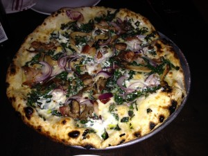 pizza topped with mushroom, pancetta, asiago, tallegio, kale, mascarpone, red onion