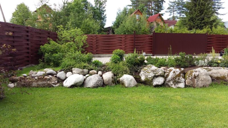 Пример ландшафта от хохлов. На этом месте был жуткий лес с этими камнями. Сейчас мощеная площадка под 3 машины, газон и рокарий. Забор тоже от них.