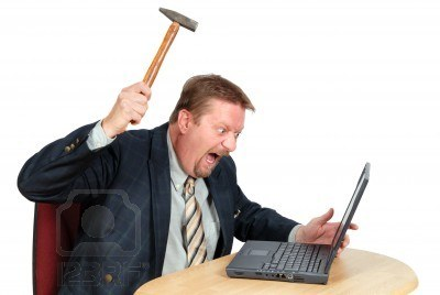 1676559-frustrated-user-or-businessman-in-his-office-threatening-to-destroy-his-pc-with-a-hammer-out-of-shee