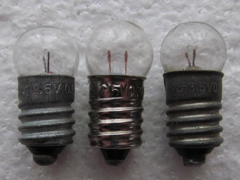 в центре фотографии современная миниатюрная  лампочка накаливания на 2,5 В
