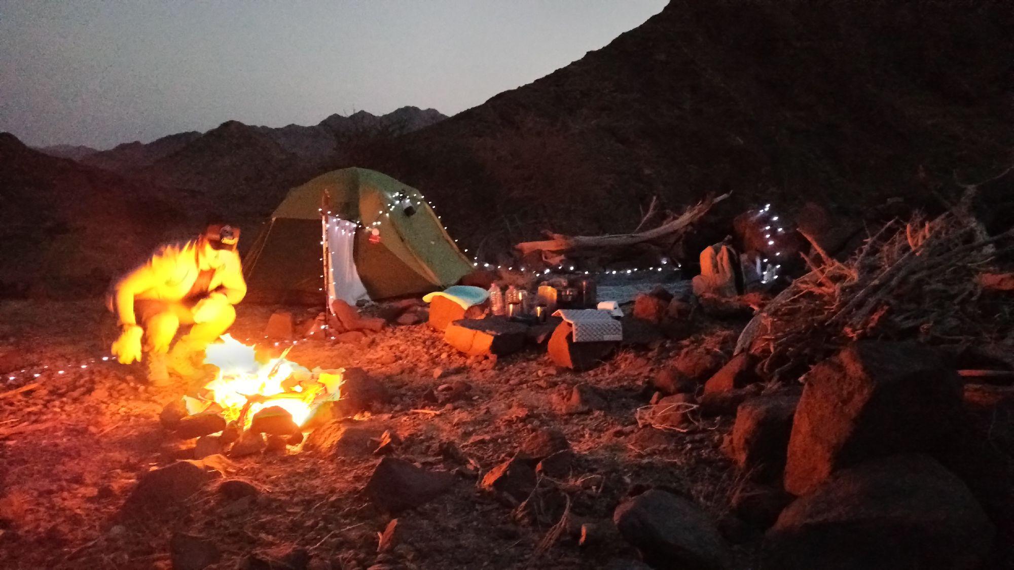Организация лагеря: палатка, подвешенный на нее экран, чуть ближе к костру стол и стулья из камней, за ним зона для валяния с ковриками