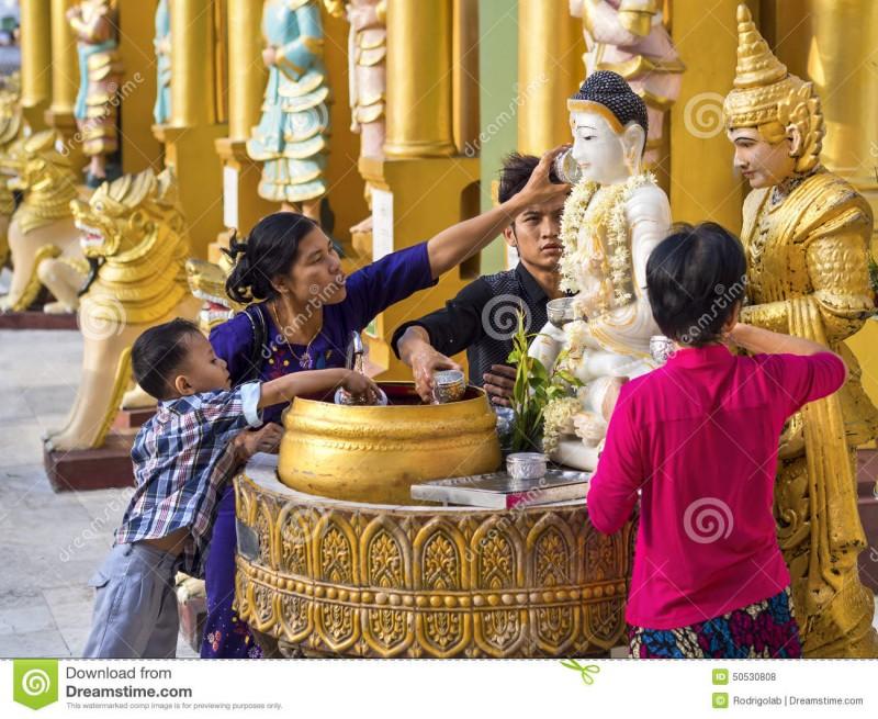 Верующие поливают сладкой водой статуи духов-натов - божеств буддийского пантеона