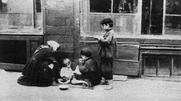 Крестьянка с детьми, сбежавшие от голода, на улице Киева. Фото 1933 г.