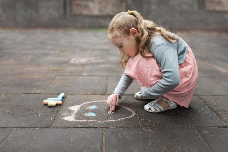 girl-in-a-pink-dress-drawing-chalk-on-pavement-low-res