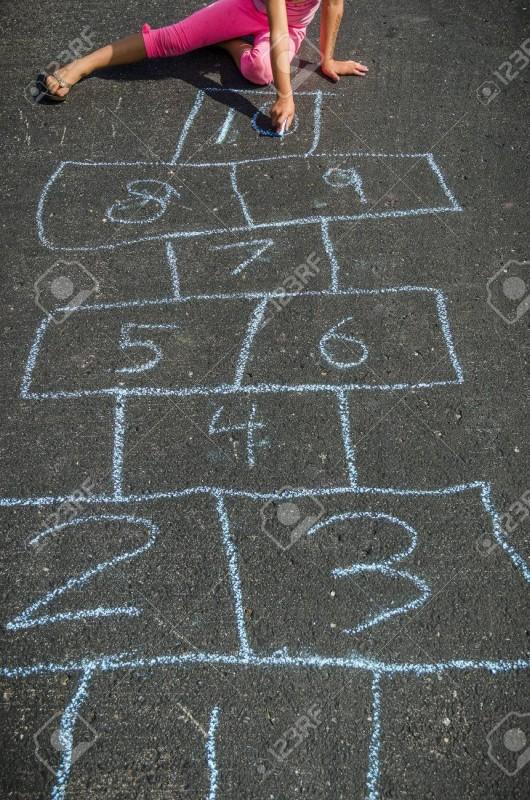 43355506-mädchen-zeichnung-mit-kreide-draußen-spielen-himmel-und-hölle
