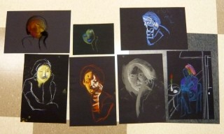 brightly colored portrait head drawings on black paper