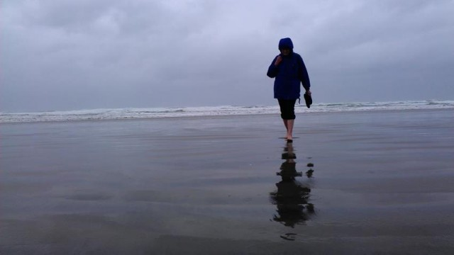 photograph of Honoria Starbuck walking on an Oregon Coast beach.