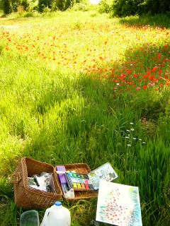 photo of art basket, paints, water, and poppy field