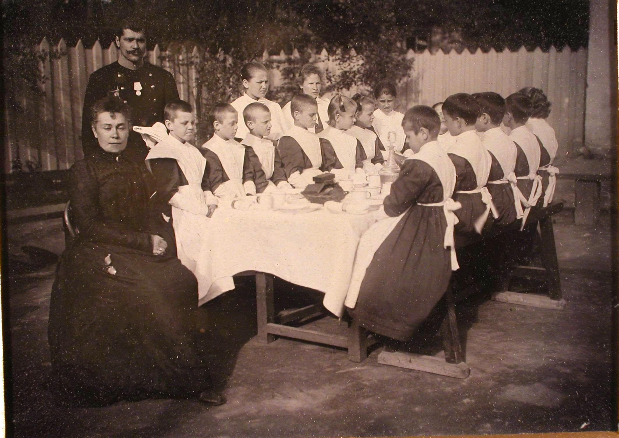 Группа воспитанниц женского отделения школы с учителем за чайным столом