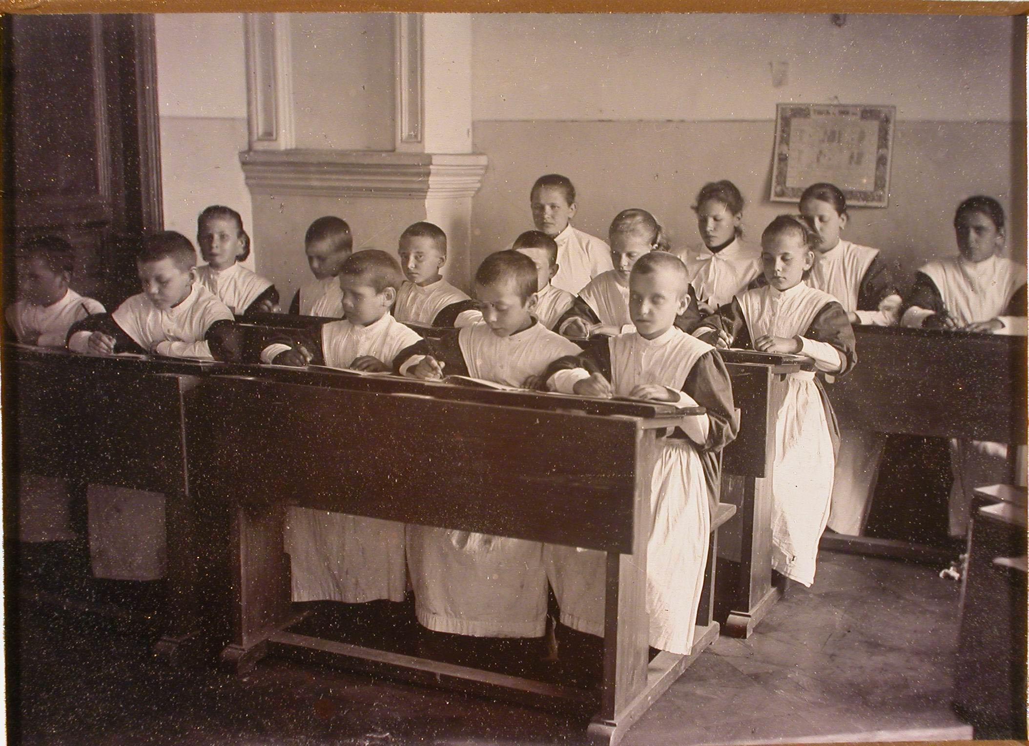 Группа воспитанниц школы во время урока в классе.