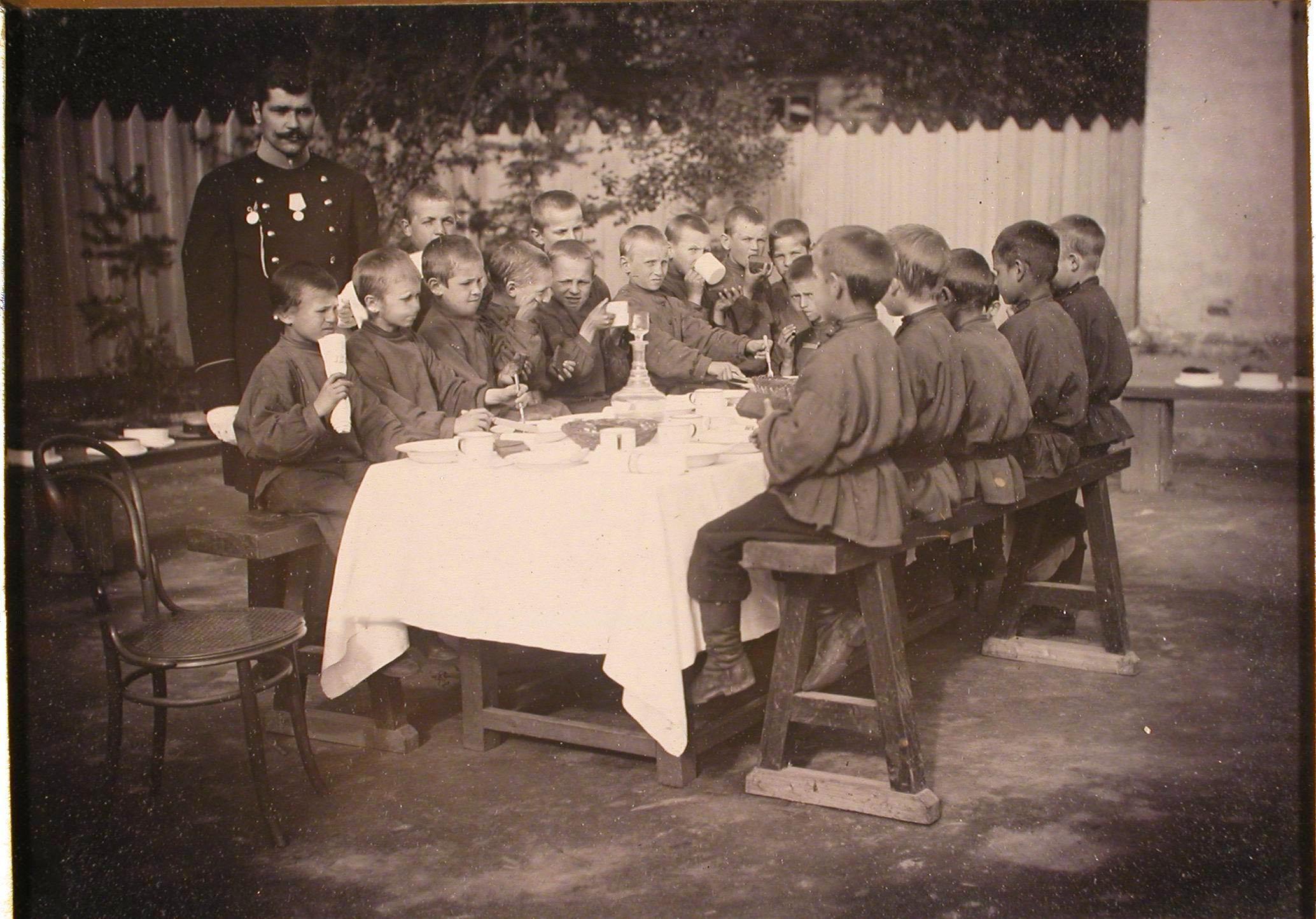 Группа мальчиков-воспитанников школы за чайным столом.