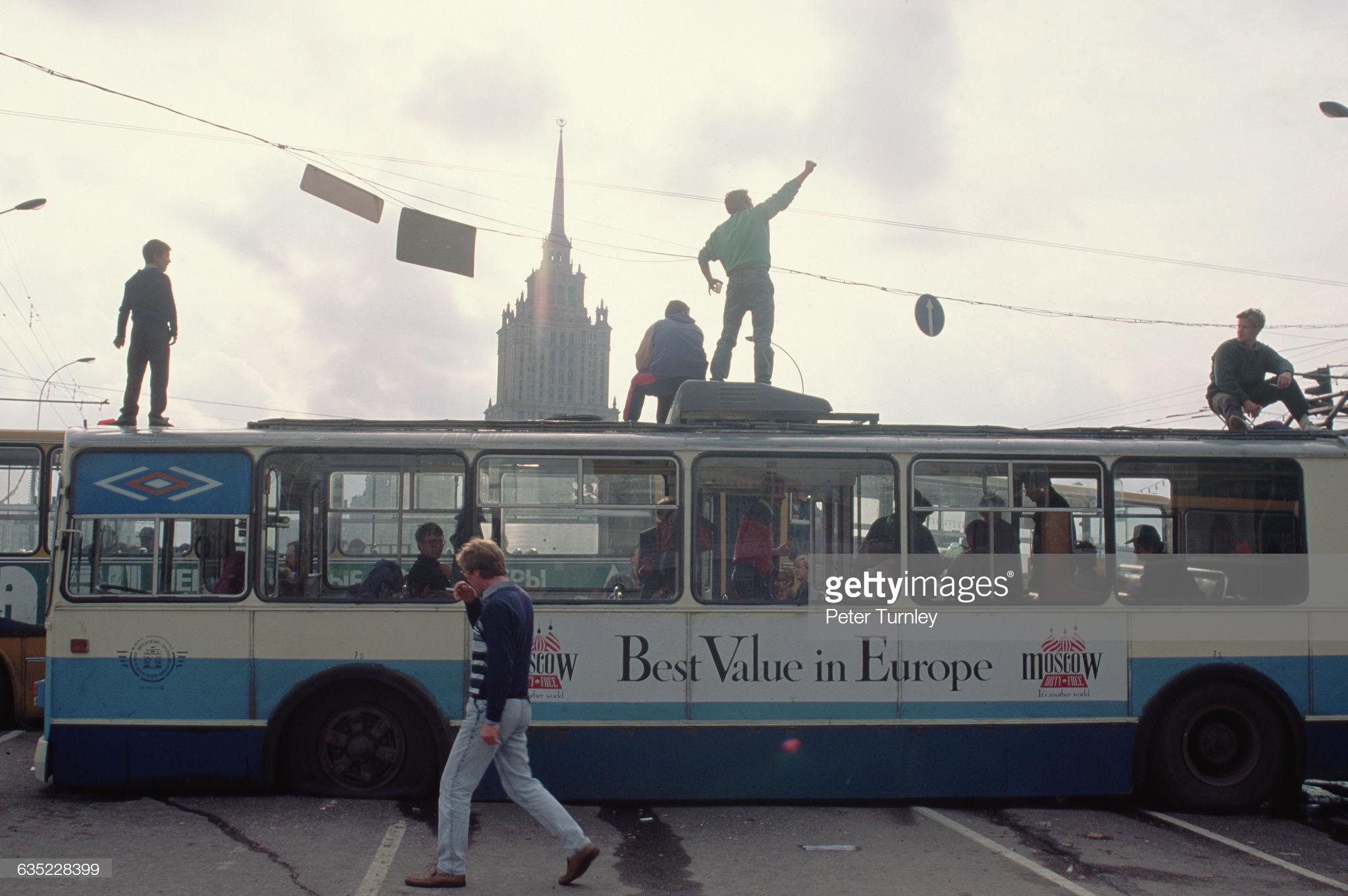 Люди стоят на крышах автобусов, которые используются в качестве баррикад для блокировки доступа на Красную площадь