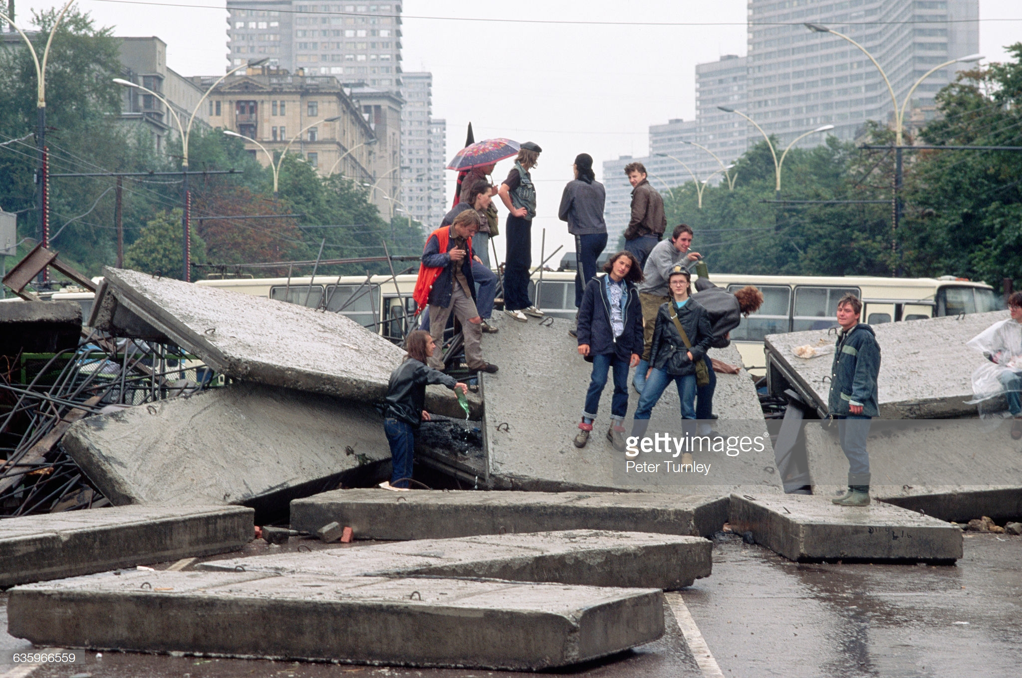 Небольшая группа подростков на больших плитах сломанного тротуара