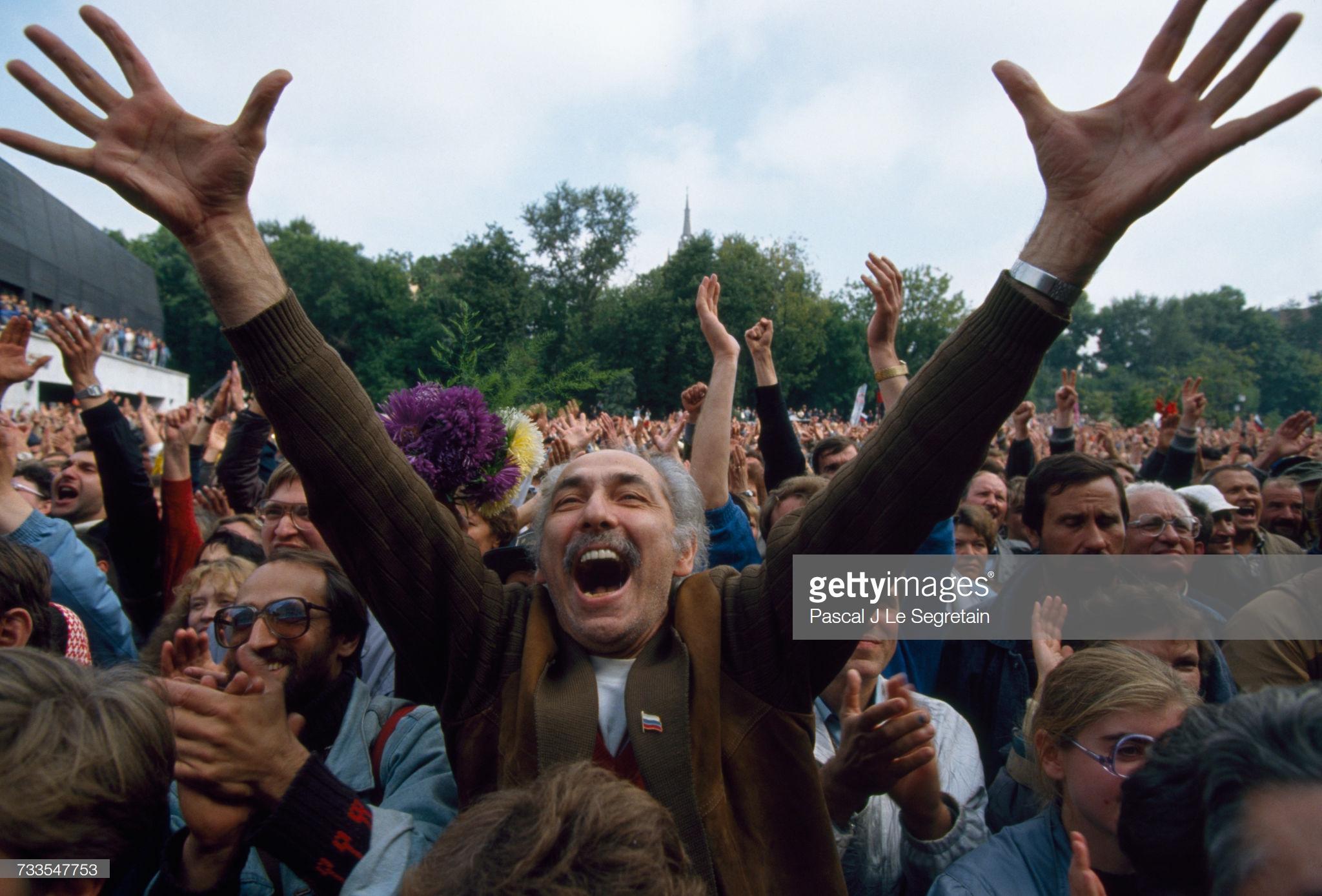Группа демонстрантов, собравшаяся перед зданием парламента, приветствует обращение  Бориса Ельцина, демократически избранного в июле 1991