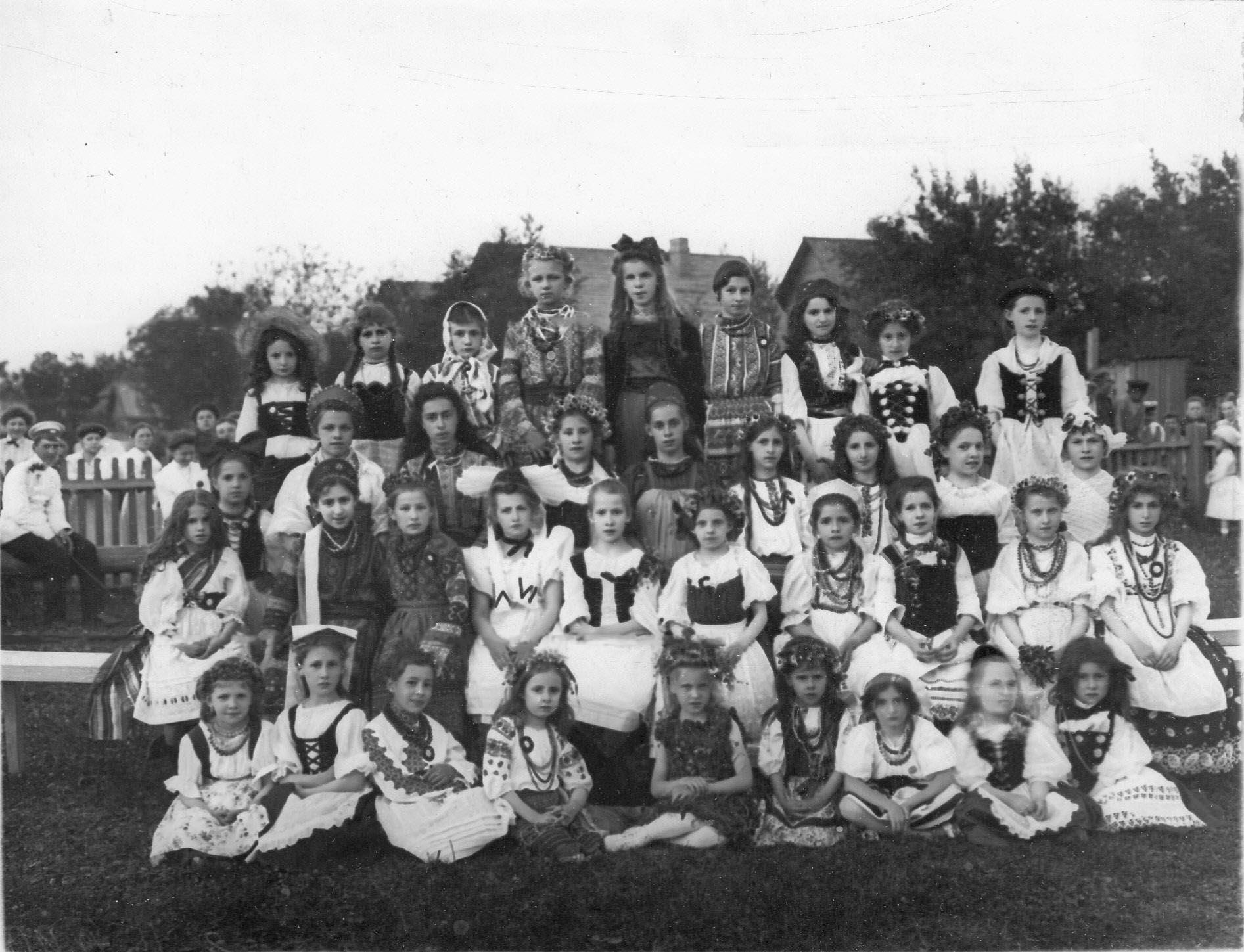 Группа детей в национальных костюмах на спортивной площадке гимнастического общества Пальма