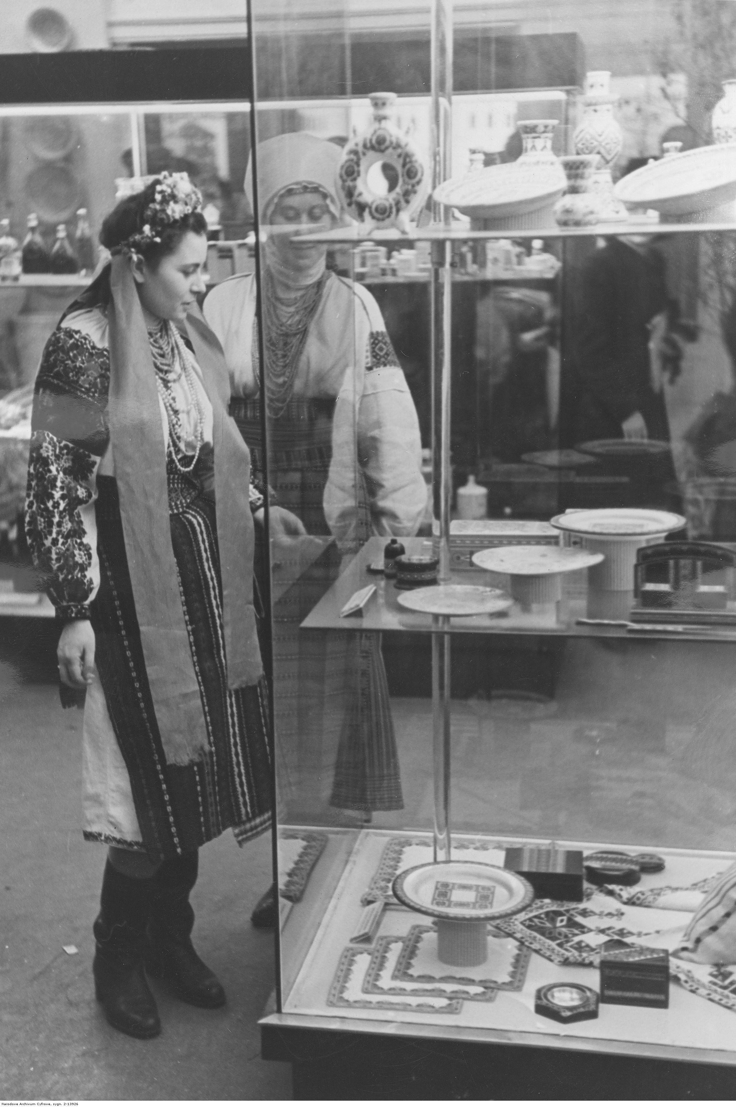 1941. Лейпцигская ярмарка. Украинская девушка в народном костюме показывает посетителям продукты украинского производства