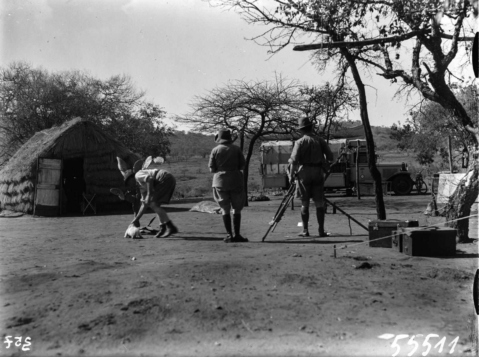 Южно-Африканский Союз. В окрестностях Претории. Участники экспедиции снимают в поселении. Шомбургк держит собаку