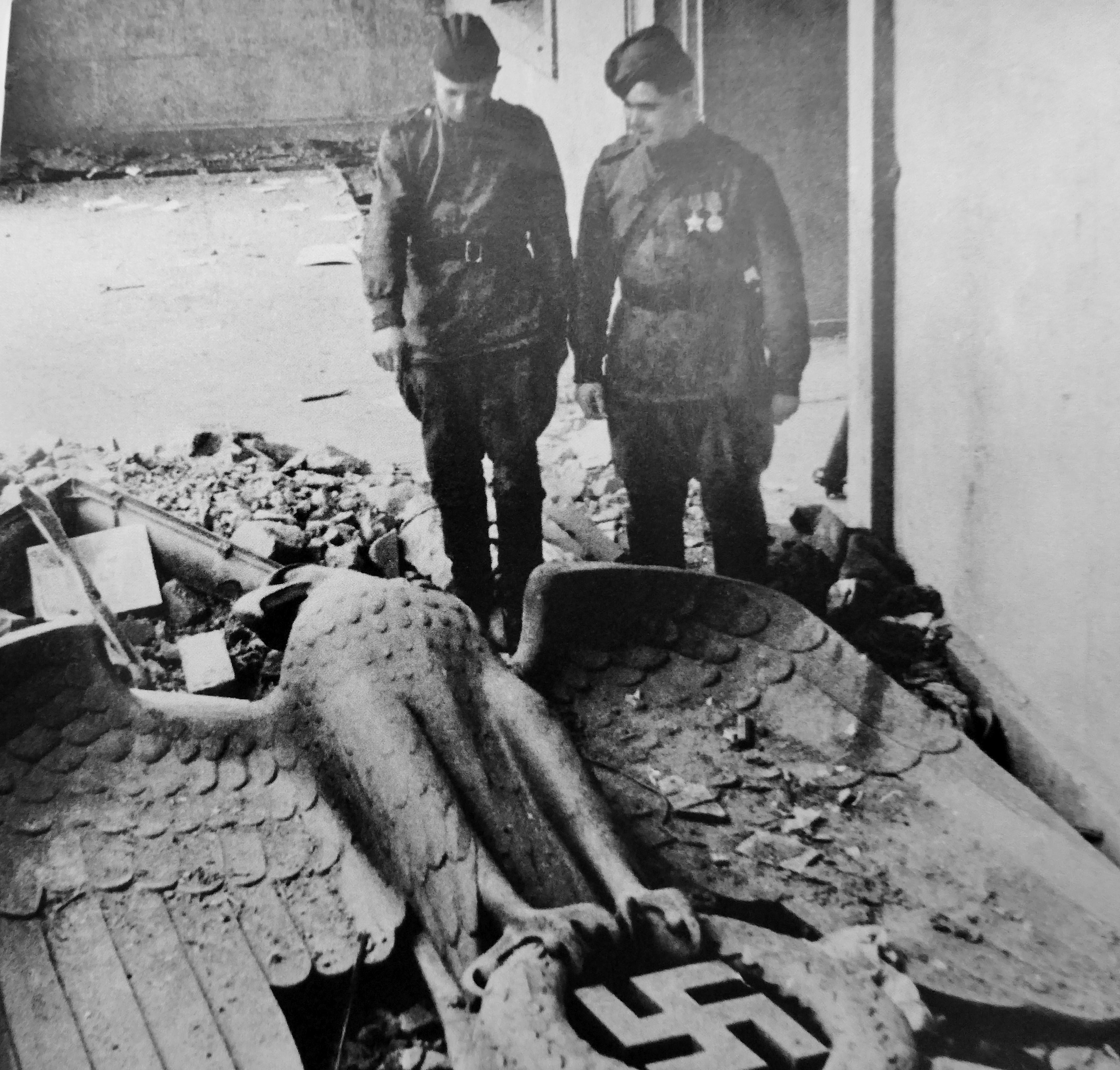 1945. Красноармейцы смотрят на имперского бронзового орла, сбитого со стены новой имперской канцелярии в Берлине
