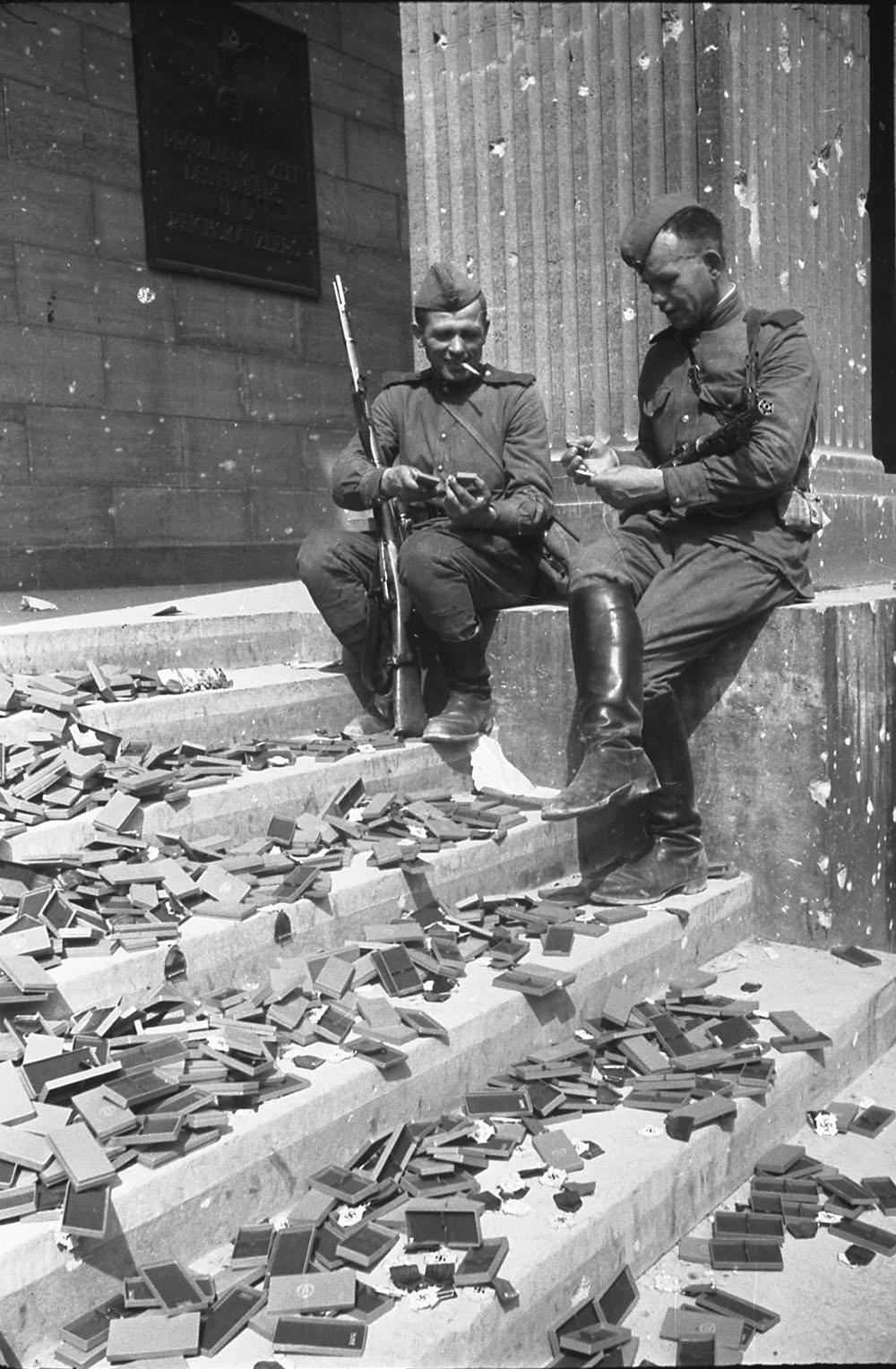 1945. Советские солдаты, отдыхая на ступенях рейхсканцелярии, рассматривают немецкие награды, которые так и не были вручены. Берлин. 2 мая
