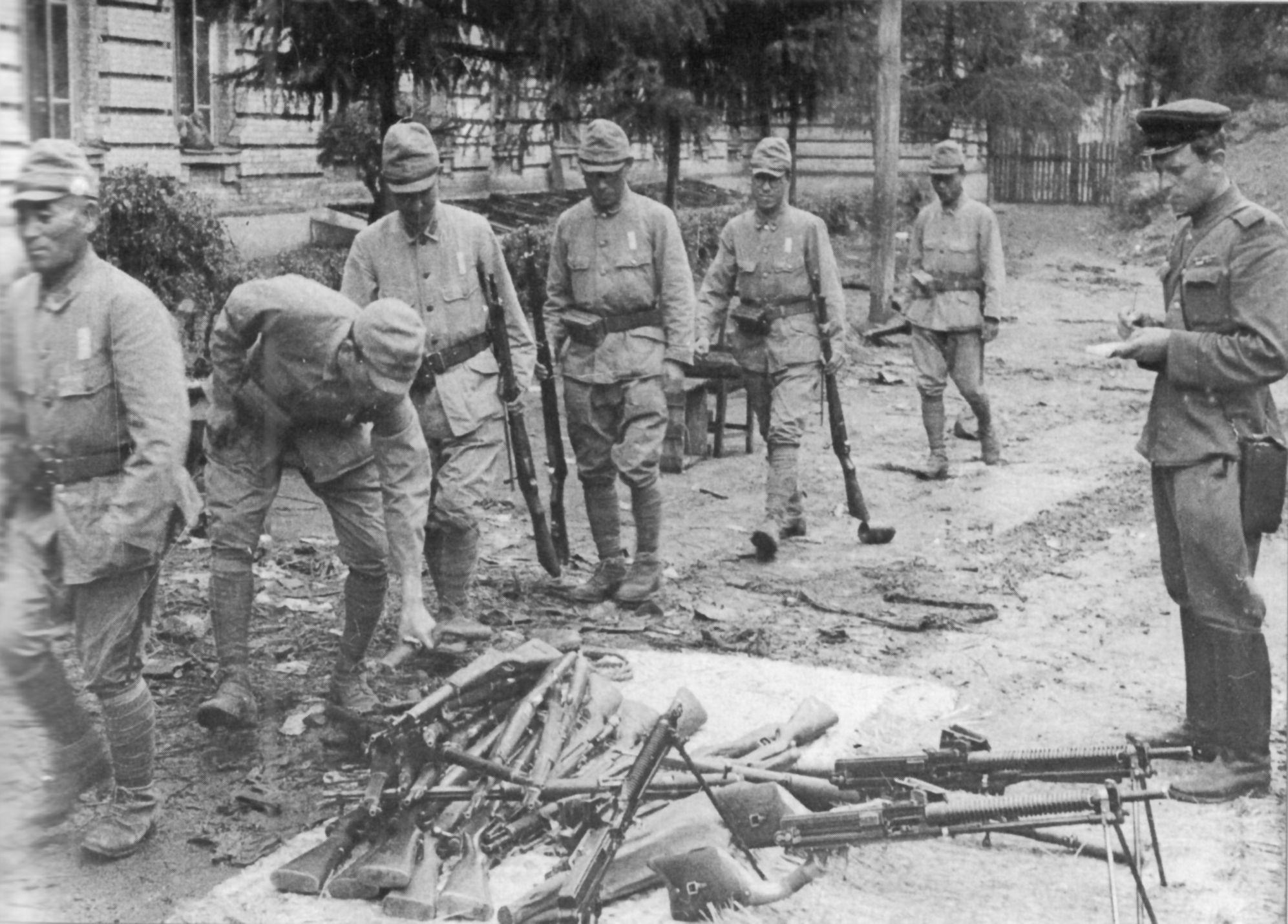 1945. Японские солдаты сдают свое оружие советскому офицеру.
