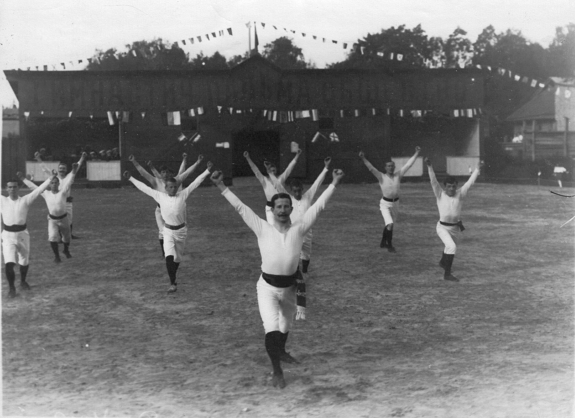 Группа членов Гимнастического общества «Пальма» делает упражнения на спортивной площадке