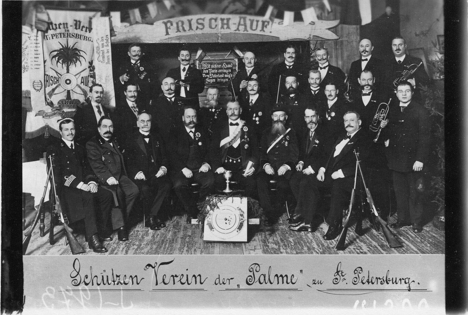 Победители состязаний по стрельбе с наградами на сцене зала Гимнастического общества «Пальма» во время их чествования