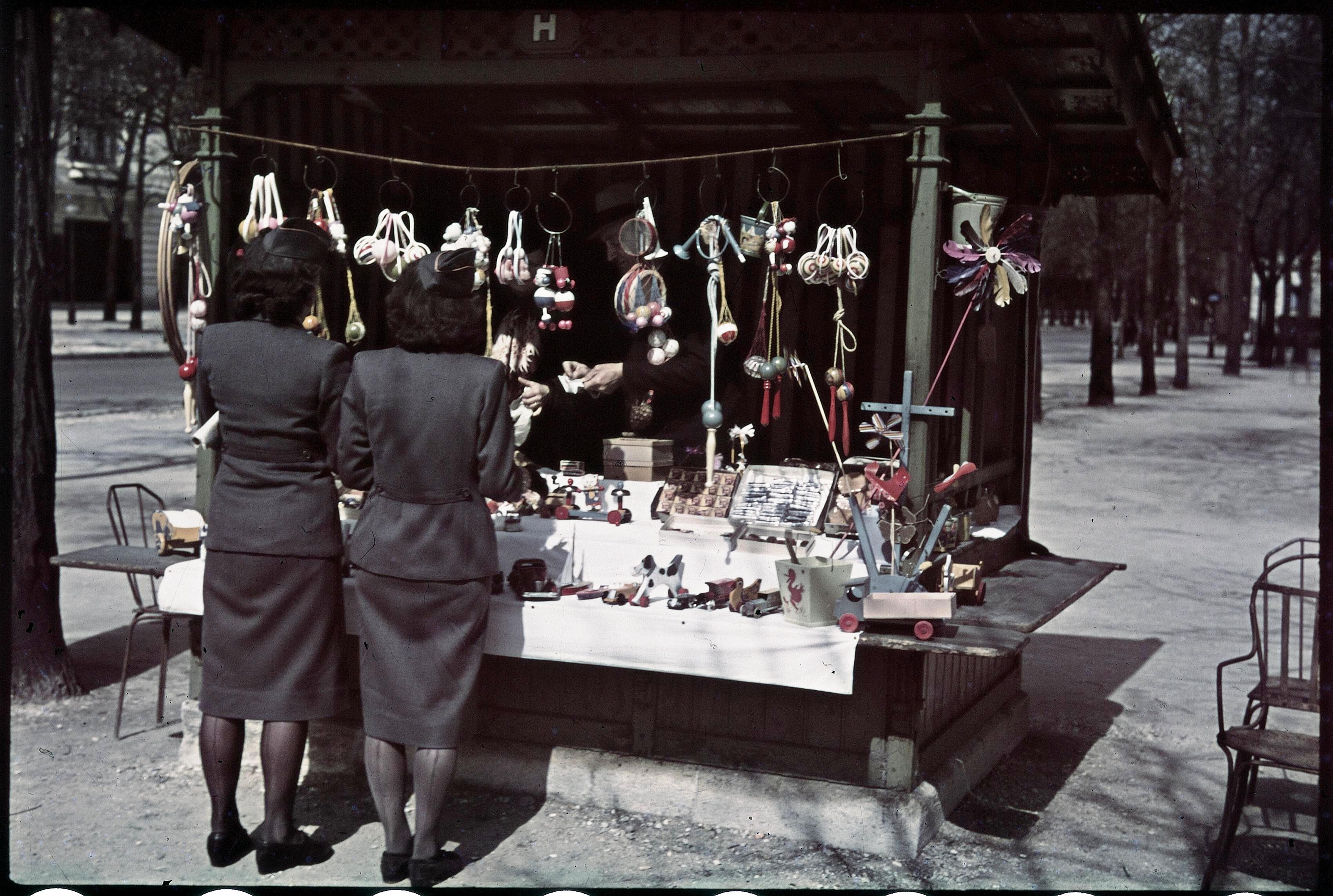 «Серые мыши» («Helferinen», женский вспомогательный подраздел СС) перед киоском с игрушками на Елисейских полях
