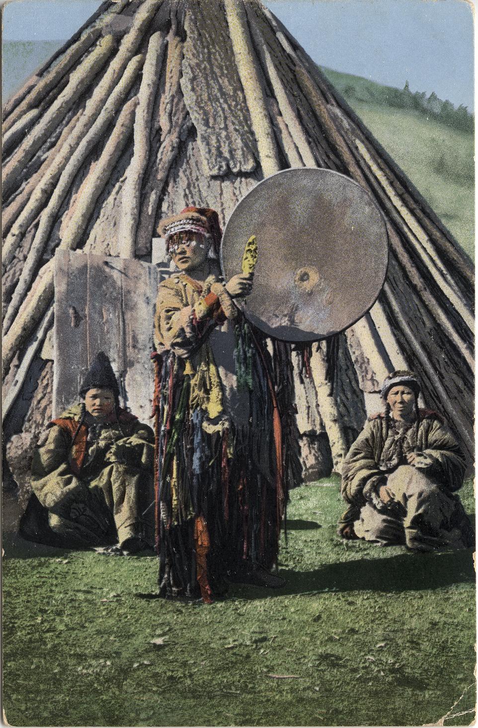 Алтайский шаман с бубном на фоне традиционного жилища - чаадыр