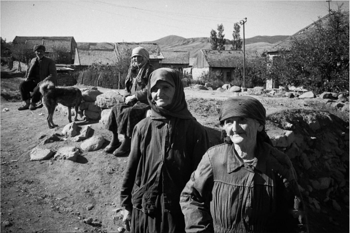Пожилые женщины и мужчина на улице деревни.